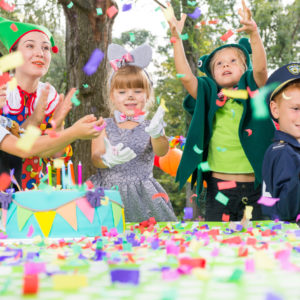 Children wearing funny costumes during outdoor birthday party